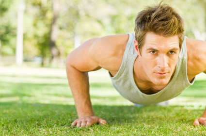 Physically fit man doing push-ups at the park